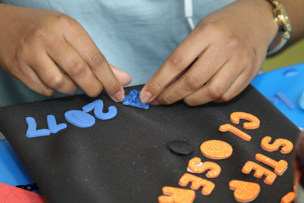 Student decorating their cap